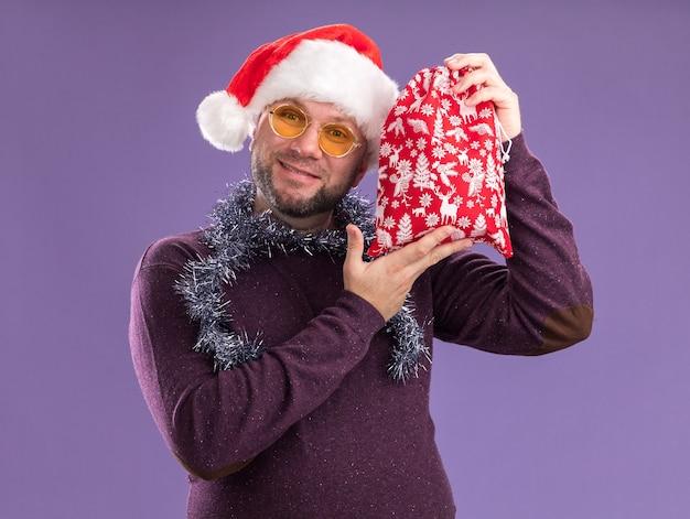 Довольный мужчина средних лет в новогодней шапке и мишурной гирлянде на шее в очках, держащий рождественский подарочный мешок возле головы, изолированный на фиолетовой стене
