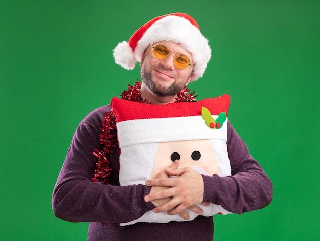 Довольный мужчина средних лет в шляпе санта-клауса и гирлянде из мишуры на шее в очках с подушкой санта-клауса, изолированной на зеленой стене