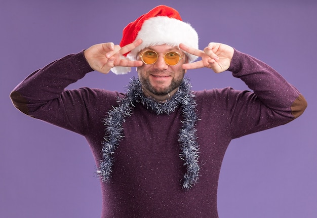 V 기호 기호를 보여주는 카메라를보고 안경 목에 산타 모자와 반짝이 갈 랜드를 입고 기쁘게 중년 남자