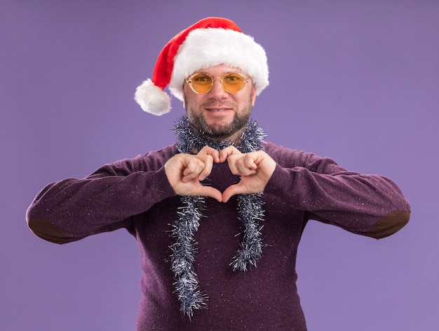 Pleased middle-aged man wearing santa hat and tinsel garland around neck with glasses  doing heart sign isolated on purple wall