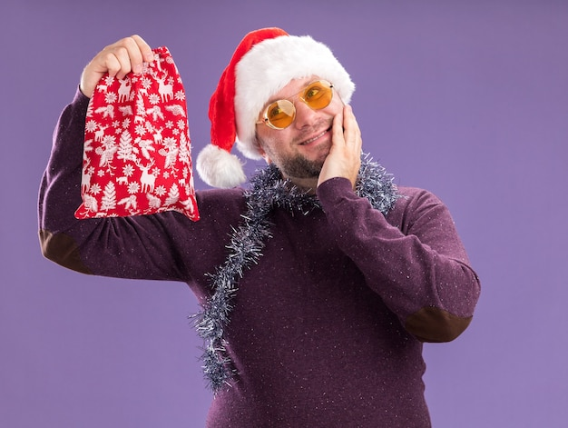 Pleased middle-aged man wearing santa hat and tinsel garland around neck with glasses holding christmas gift sack looking at side keeping hand on face isolated on purple background