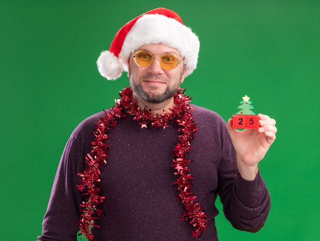 Pleased middle-aged man wearing santa hat and tinsel garland around neck with glasses holding christmas tree toy with date  isolated on green wall