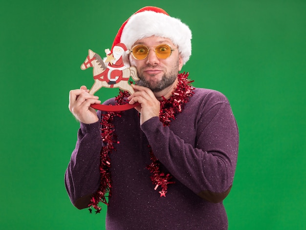 Pleased middle-aged man wearing santa hat and tinsel garland around neck with glasses holding santa on rocking horse figurine touching head with it  isolated on green wall