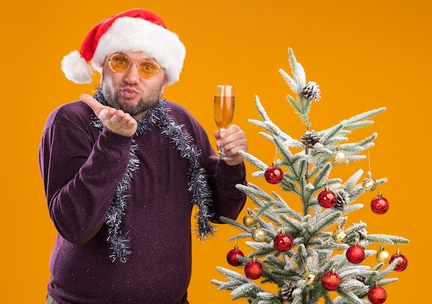 Pleased middle-aged man wearing santa hat and tinsel garland around neck with glasses standing near decorated christmas tree holding glass of champagne