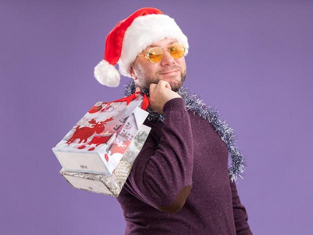 Felice uomo di mezza età che indossa un cappello da babbo natale e una ghirlanda di orpelli intorno al collo con gli occhiali in piedi in vista di profilo tenendo i sacchetti regalo di natale sulla spalla guardando la telecamera isolata su sfondo viola