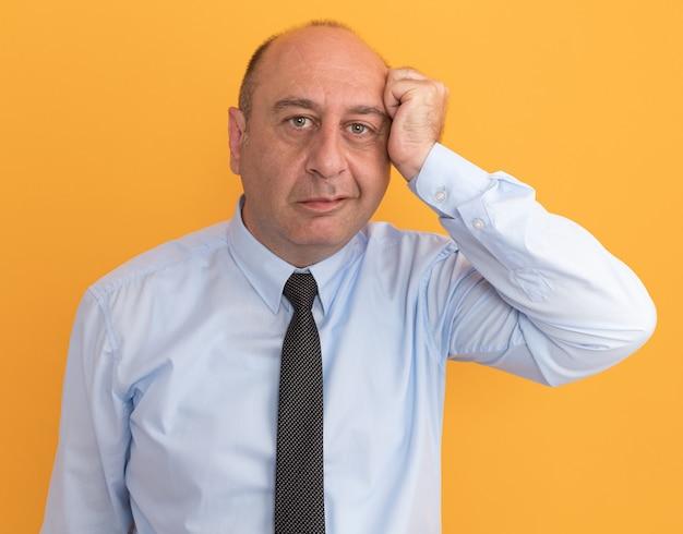오렌지 벽에 고립 된 사원에 주먹을 넣어 넥타이와 흰색 티셔츠를 입고 기쁘게 중년 남자