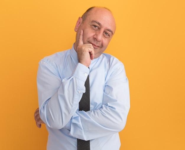 Soddisfatto uomo di mezza età che indossa la maglietta bianca con cravatta mettendo la mano sulla guancia isolata sulla parete arancione