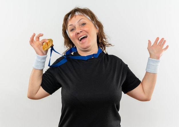 Pleased middle aged sporty woman in black t-shirt with headband and gold medal around her neck showing it smiling cheerfully standing over white wall
