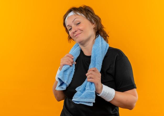 Lieta donna sportiva di mezza età in maglietta nera con fascia e con asciugamano sulla spalla con un sorriso fiducioso sul viso in piedi sopra la parete arancione
