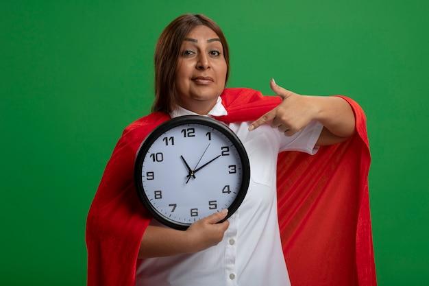 Довольный женщина супергероя средних лет держит и указывает на настенные часы, изолированные на зеленом фоне
