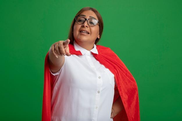 緑の背景に分離されたジェスチャーを示す眼鏡をかけている中年のスーパーヒーローの女性