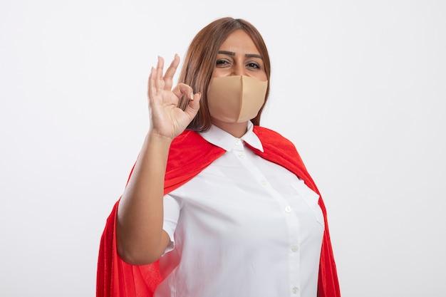白で隔離された大丈夫なジェスチャーを示す医療マスクを身に着けている満足している中年のスーパーヒーローの女性