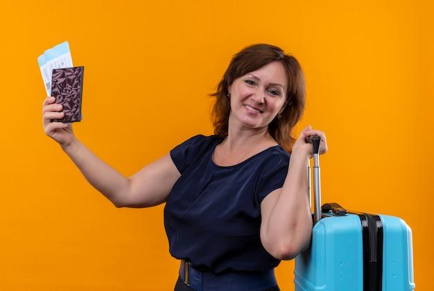 孤立したオレンジ色の壁にスーツケースとチケットと財布を保持している中年の旅行者の女性を喜ばせる