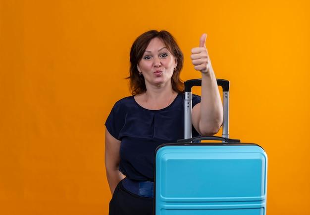 孤立したオレンジ色の壁に彼女の親指をスーツケースに手を置く中年の旅行者の女性を喜ばせる