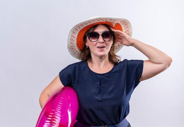 Piacevole viaggiatore di mezza età donna con gli occhiali con cappello che tiene l'anello gonfiabile sulla parete bianca isolata