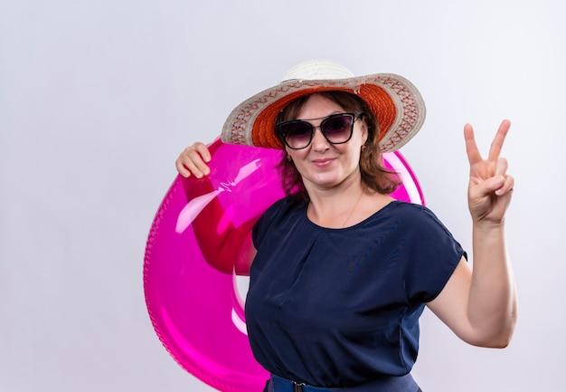 Довольная женщина-путешественница средних лет в очках и шляпе держит надувное кольцо, показывая жест мира на изолированной белой стене
