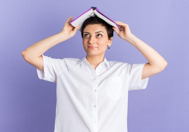 Donna di mezza età contenta che tiene il libro aperto sulla testa che guarda in su