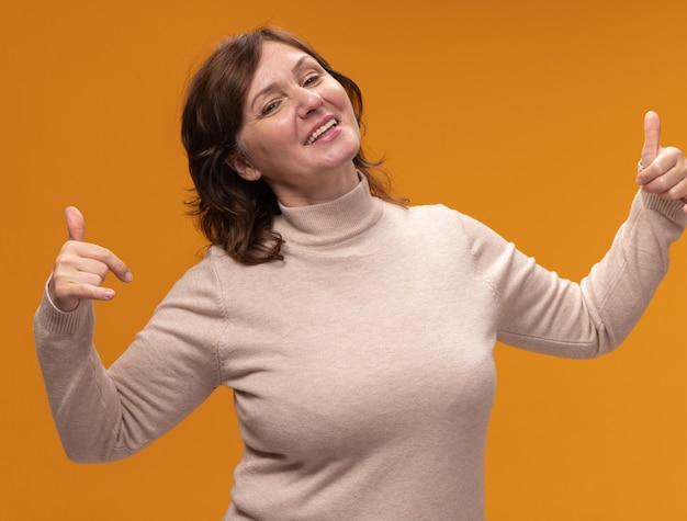 オレンジ色の壁の上に立って幸せで陽気な自分自身を指しているベージュのタートルネックで満足している中年の女性