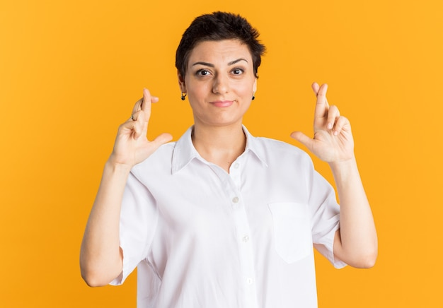Pleased middle-aged woman looking at camera doing good luck gesture