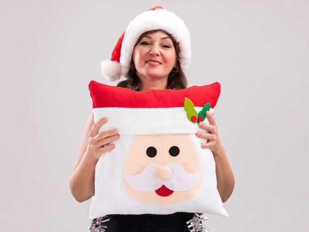 Довольная женщина средних лет в шляпе санта-клауса и гирлянде из мишуры на шее держит подушку санта-клауса, глядя в камеру, изолированную на белом фоне