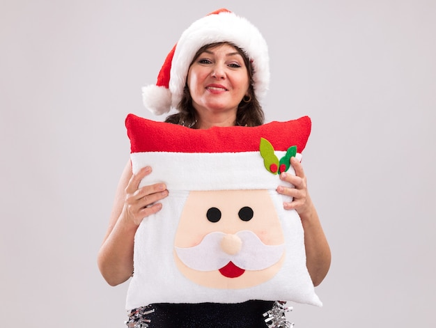 Pleased middle-aged woman wearing santa hat and tinsel garland around neck holding santa claus pillow looking at camera isolated on white background