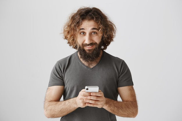 Pleased middle-eastern bearded man satisfied, using mobile phone