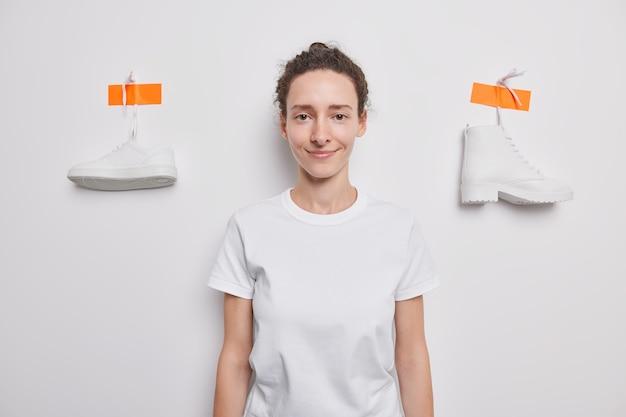 Довольная миллениальная девушка в повседневной футболке позирует на фоне белой стены в пластиковых туфлях, выбирает между кроссовками и сапогами, смотрит прямо вперед.