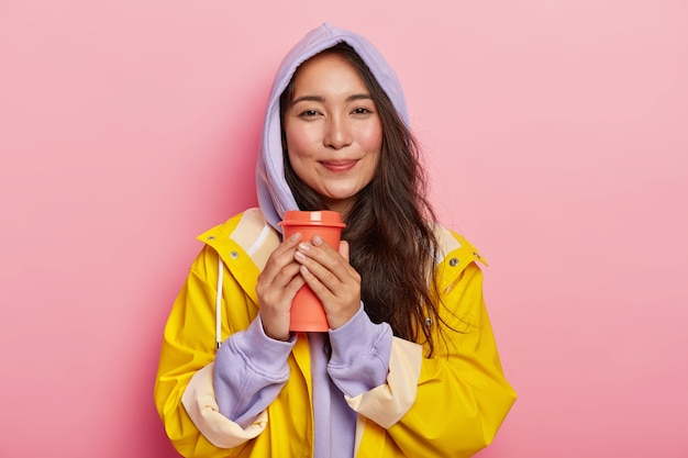 Pleased millennial girl with asian appearance, has no makeup, wears violet sweatshirt and raincoat, holds flask with hot beverage, tries to warm while drinking tea