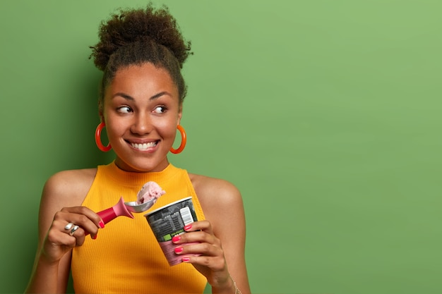 Pleased millennial girl with curly hair, bites lips and eats delicious ice cream with appetite, enjoys natural flavor, chills during summer day, looks gladfully aside, empty space on green wall