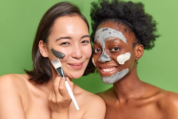 満足している混血の女性が美容マスクを適用し、化粧ブラシスタンドを互いに密接に使用してきれいにします