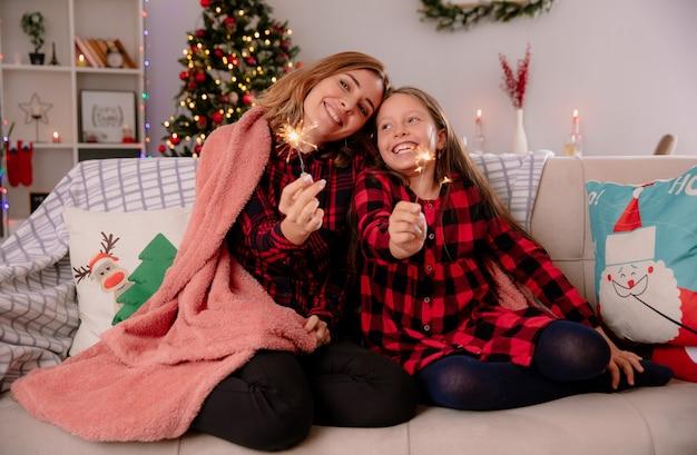 Довольные мать и дочь держат бенгальские огни, накрытые одеялом, сидя на диване и наслаждаясь рождеством дома