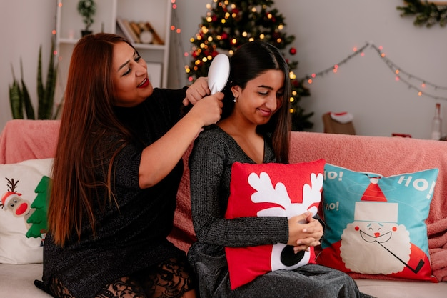 Pleased mother combing daughter hair sitting on couch enjoying christmas time at home