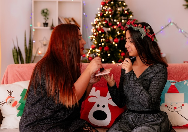 Felice madre e figlia che fanno trucco seduto sul divano godendo il periodo natalizio a casa