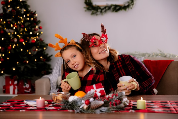 Pleased mother and daughter holding cup sitting at table enjoying the christmas time at home