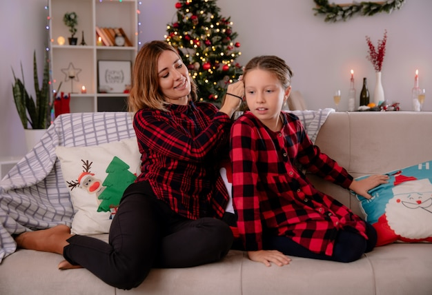Pleased mother looks and braids her daughter hair sitting on couch and enjoying christmas time at home
