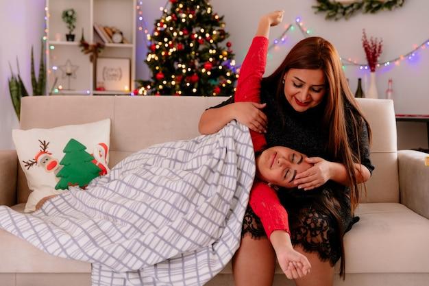 소파에 앉아 기쁘게 어머니는 집에서 크리스마스 시간을 즐기고 팔을 열어 담요에 싸여 무릎에 자고있는 딸을 봅니다.