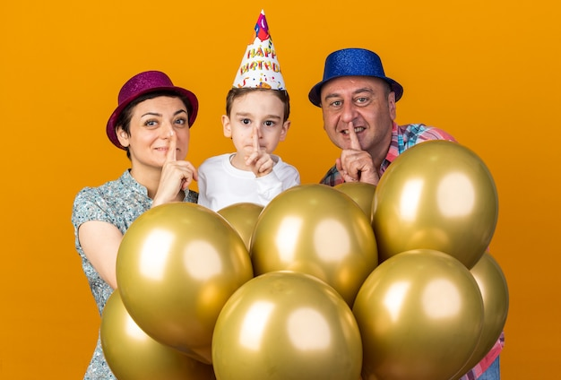 Pleased mother son and father wearing party hats standing with helium balloons doing silence gesture isolated on orange wall with copy space