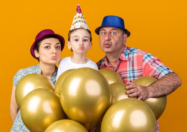 Pleased mother son and father wearing party hats standing with helium balloons pretending to kiss isolated on orange wall with copy space