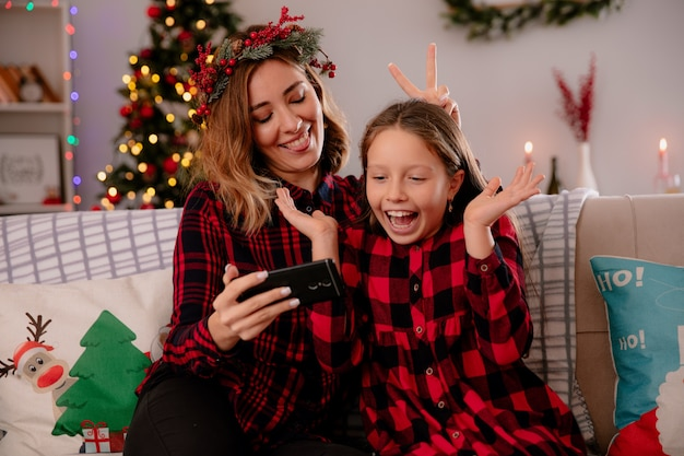 Pleased mother stucks out tongue and shows something on phone to daughter sitting on couch and enjoying christmas time at home