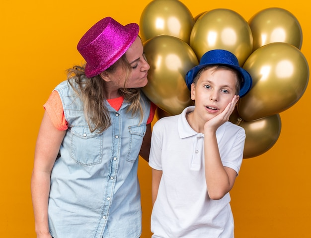 Pleased mother wearing purple party hat and holding helium balloons looking at her surprised son with blue party hat putting hand on face isolated on orange wall with copy space