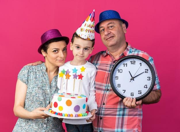 Madre contenta con cappello da festa viola che tiene la torta di compleanno e padre sorridente con cappello da festa blu che tiene l'orologio in piedi con il figlio isolato sul muro rosa con spazio di copia