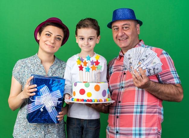 Madre contenta con cappello da festa viola che tiene in mano una scatola regalo in piedi con il figlio che tiene in mano una torta di compleanno e con il padre che indossa un cappello da festa blu e tiene in mano denaro isolato sul muro verde