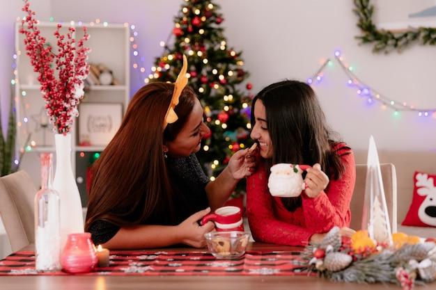 カップを保持しているトナカイのヘッドバンドを持つ満足している母親は、自宅でクリスマスの時間を楽しんでテーブルに座っているビスケットで娘を養います