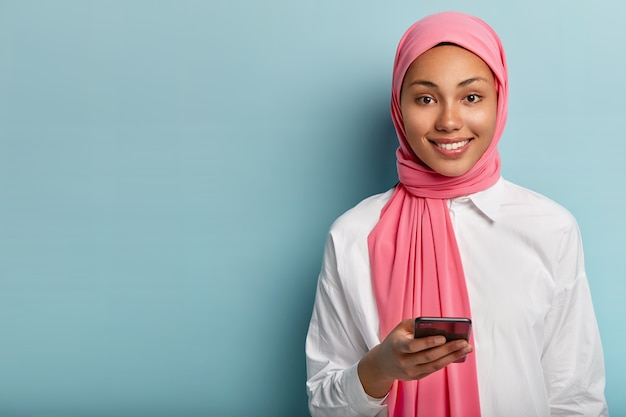 Pleased muslim woman uses cell phone to socialize, gives reply in online chat, posts something in social networks