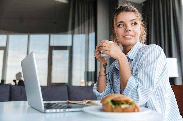 リビングルームのテーブルに座ってコーヒーを飲み、ラップトップを使用して喜んでいる素敵な女性