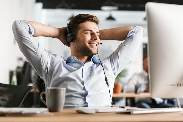 マイク付きヘッドセットで話し、オフィスのテーブルのそばに座って目をそらしているオフィスマネージャーを喜ばせます