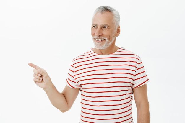 Довольный старик в футболке смотрит и указывает налево