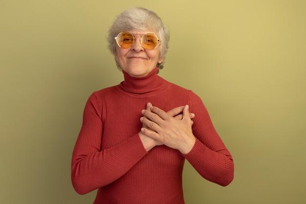 빨간 터틀넥 스웨터와 선글라스를 끼고 앞을 바라보는 행복한 노부인은 복사공간이 있는 올리브 녹색 벽에 격리된 가슴에 손을 얹고 있다