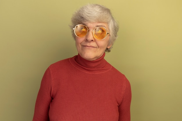 Pleased old woman wearing red turtleneck sweater and sunglasses looking up isolated on olive green wall