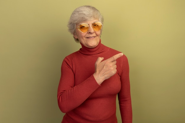 Piacevole vecchia donna che indossa un maglione a collo alto rosso e occhiali da sole che puntano a lato isolato su parete verde oliva con spazio di copia